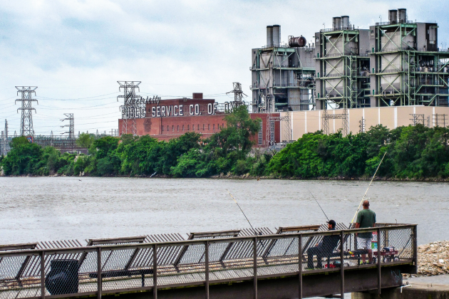 Two men fish in the Arkansas River on a pier facing the historic Public Service Co. of Oklahoma power plant in Tulsa.