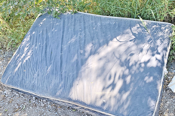 This mattress, trash bags, wooden box and broken shelves were laying in the bar ditches on either side of Railroad Street within a mile of Peacan Road on Monday.
