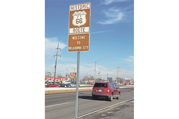 Ledger photo by Andrew W. Griffin A motorist passes by a historic Route 66 sign at an Oklahoma City boundary.