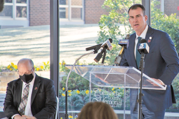 Oklahoma Gov. Kevin Stitt, right, addresses members of the press concerning the first shipment of COVID-19 vaccine sent to Comanche County Memorial Hospital in Lawton Wednesday The coronavirus is said to have been the cause of death for 306,000 people across the United States since March. Of those, 2,128 were Oklahomans, according to the Oklahoma State Department of Health's most recent numbers.