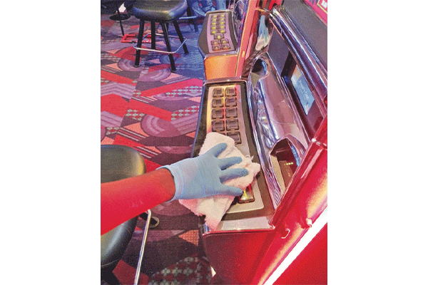 A worker wipes down a slot machine at Apache Casino Hotel in Lawton.